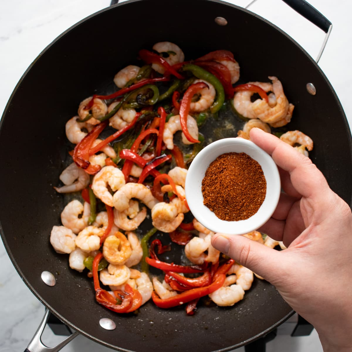 A hand holding a small white bowl of low FODMAP taco seasoning over a skillet filled with sautéed shrimp and bell pepper slices.