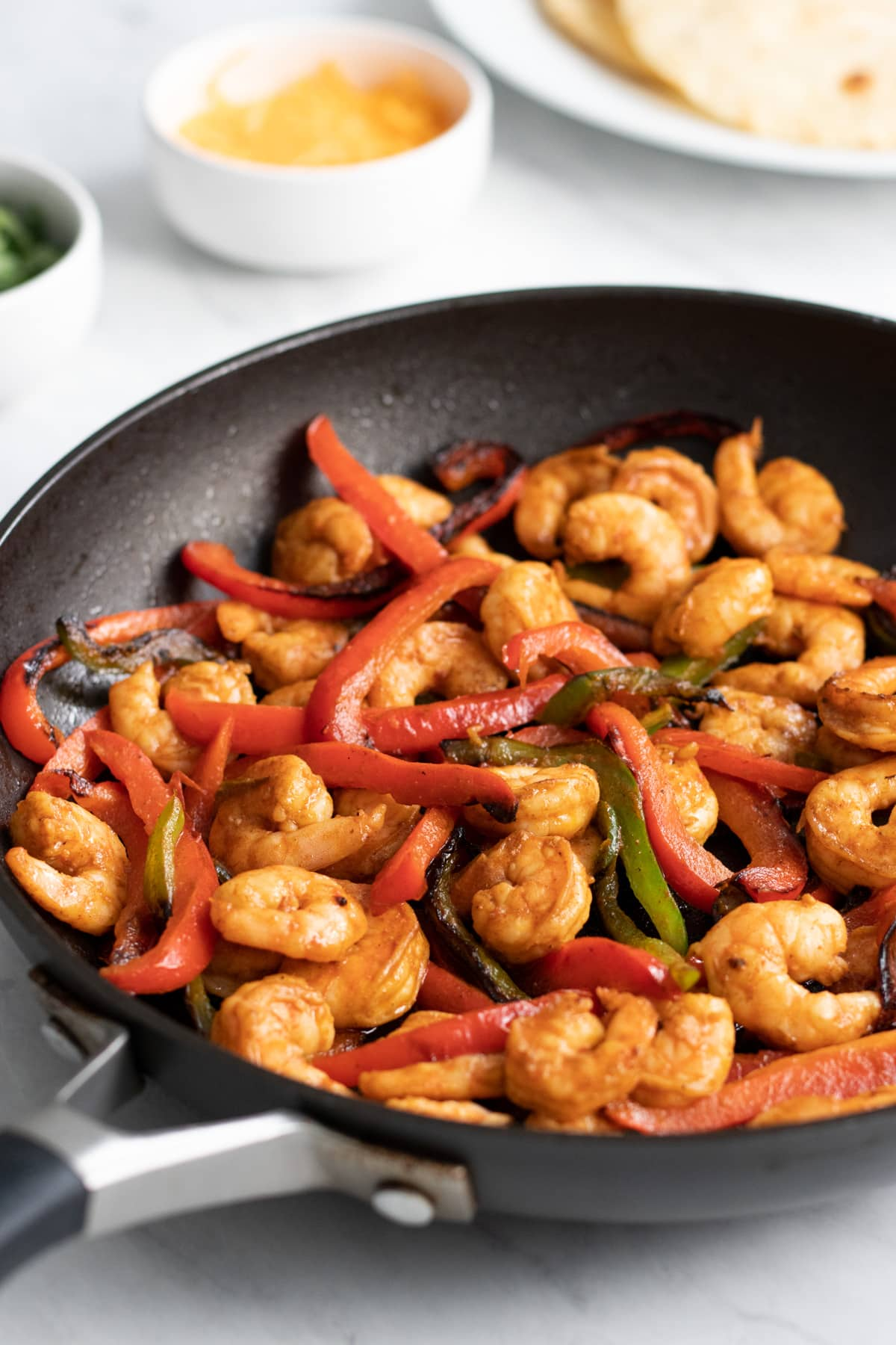 Looking into a skillet filled with low FODMAP shrimp fajitas. A plate of warm corn tortillas, and small bowls of cheddar cheese and sliced green onion tops sit in the background.