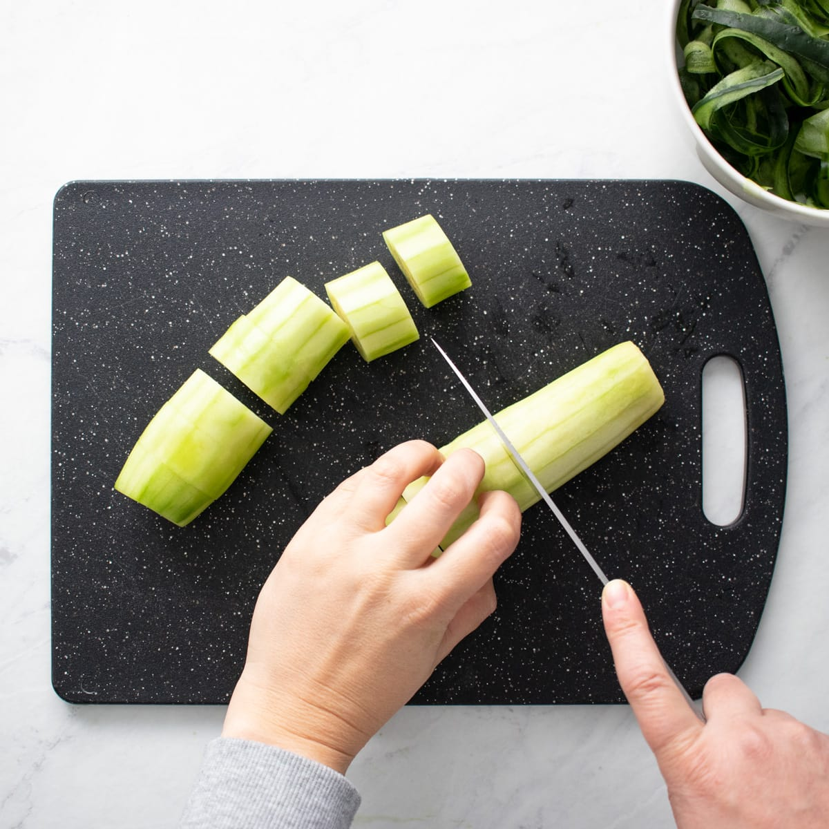 Cutting peeled cucumber into thick slices