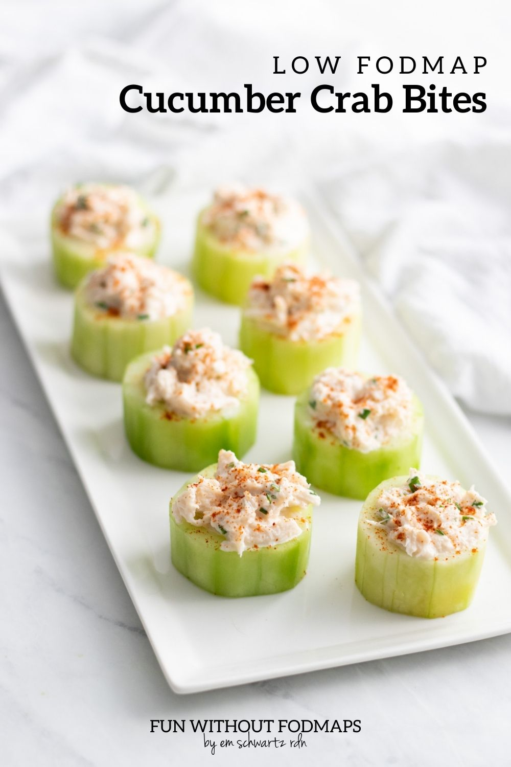 """A rectangular plate with eight cucumber cups filled with a creamy crab mixture. In the white space above, a black text overlay reads """"Low FODMAP Cucumber Crab Bites."""""""